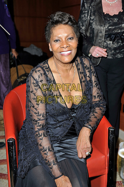 DIONNE WARWICK.attends The Hunger Project Concert after party as part of World Hunger Day 2011 at the Park Plaza Hotel in London, England, UK, January 9th, 2011..half length black dress sitting down  chair long sleeve lace  smiling cleavage boobs low cut beaded sheer jacket see thru through .CAP/MAR.© Martin Harris/Capital Pictures.