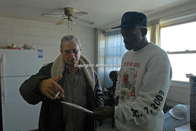 "Grant Newburger, 50, talks with Herm Willis, 49, in Willis' apartment on the eighth floor of the Cabrini Green high rise where Willis lived for years two weeks before his scheduled eviction in Chicago, Illinois on February 29, 2008.  Willis was evicted from Cabrini Green because of a ""one-strike rule"" that forbids public housing tenants caught with illicit substances from maintaining a lease; while Willis was not caught with anything, a member of his household was."