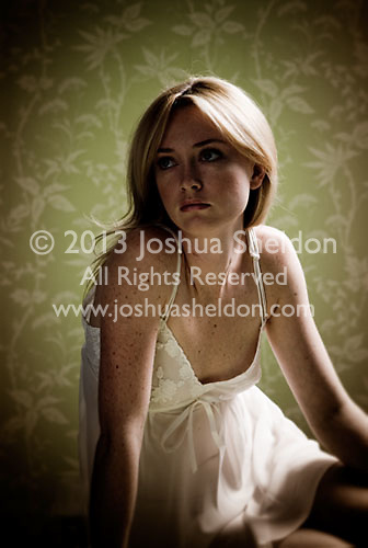 Blonde woman wearing a negligee sitting in front of floral wallpaper