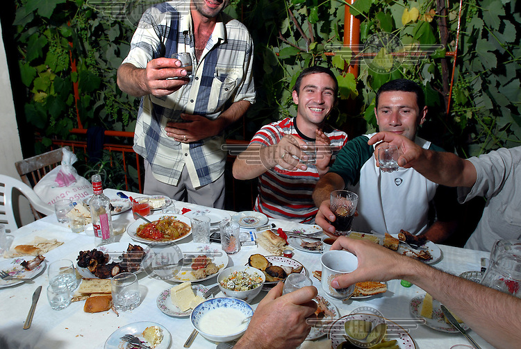A group of friends drink a toast with their home-made vodka. Home production of fruit-based alcohol is a popular pastime in Goris.