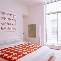 The bed cover with a red background and white crosses provides a focal point in this otherwise white bedroom