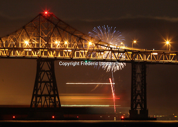 Seasonal July fireworks explodes under the Richmond San Rafael Bridge in California.