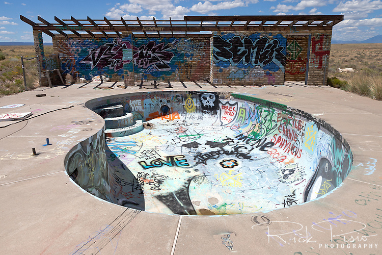 """Graffiti filled pool at the Two Guns campground in Arizona. Two Guns is located in Arizona, east of Flagstaff, on what was formerly Route 66. Two Guns was originally called """"Canyon Lodge"""" when the National Trail Highway moved westward. Later, the National Trail was re-named Route 66, the site's name was changed to Two Guns, because the proprietor of the facilities located there was one Henry E. Miller, who called himself """"Two Gun Miller."""" During the heyday of Route 66, Two Guns became one of the numerous tourist traps along the way, with a gas station, overnighting accommodations, a food emporium, as well as a zoo. Two Guns went into decline with the building of the Interstate."""