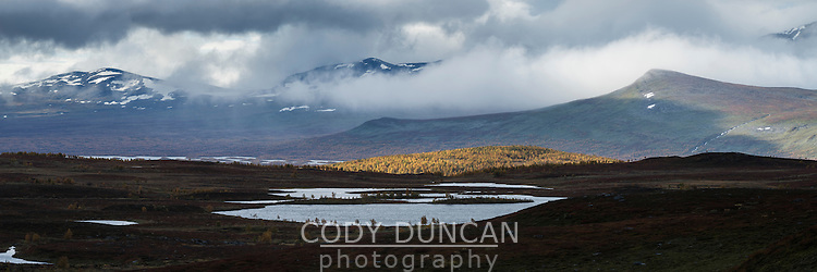 Small mountain lake with distant mountains in clouds, near Tärnasjös hut, Kungsleden trail, Lapland, Sweden