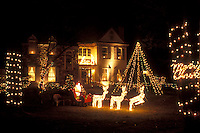 Pennsylvania, Christmas lights and figurines decorate the front yard of a large house in the evening in Berwyn.