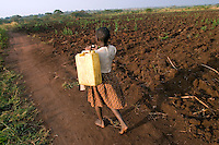 Empowering Victims of War- A young girl going to retrieve water. Canaan Family Farm lends land to displaced people from the Northern conflict to have them learn the benefits of work and empowerment. Rwakayata, Masindi, Uganda, Africa. December 2005 © Stephen Blake Farrington