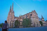 The Saint Andre Cathedral 11th 12th century with its majestic twin gothic towers in the evening at sunset on the place pey berland in Bordeaux, one young woman waiting on the square city Bordeaux Gironde Aquitaine France