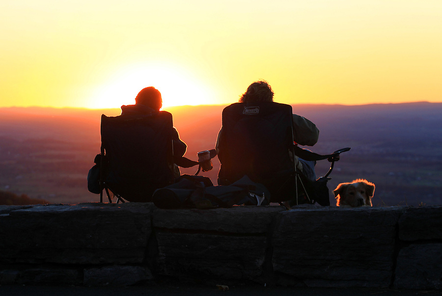 People are silhouetted as they watch the sunset from the Shenandoah National Park near Madison County, Virginia. Photo/Andrew Shurtleff