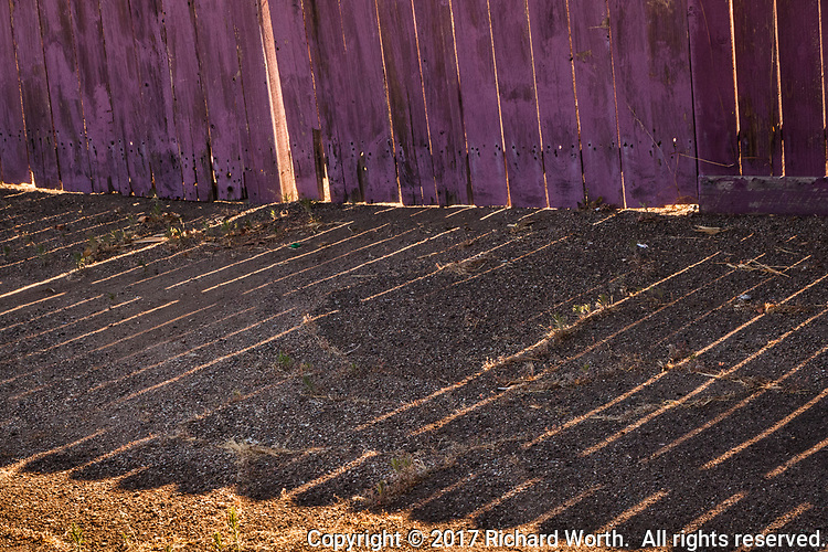 Sunlight on an urban neighborhood fence creates an urban abstract of shadows and lines.