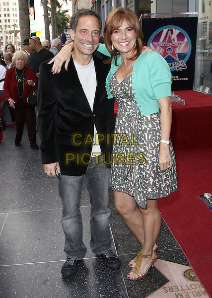 HARVEY LEVIN & MARILYN MILIAN.Judge Joseph A. Wapner - 90th Birthday celebration and honoring him with 2,392nd Star on the Hollywood Walk of Fame held At The Four Season Hotel, Hollywood, California, USA, 12th November 2009..full length grey gray suit black jacket print dress green cardigan arm around shoulder jeans brown open toe sandals .CAP/ADM/KB.©Kevan Brooks/AdMedia/Capital Pictures.