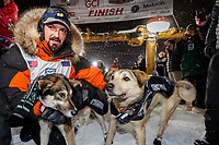 Pete Kaiser congratulates his lead dogs at the Nome finish line shortly after winning the 2019 Iditarod Trail Sled Dog Race. Pete's winning time is 9 days 12 hours 39 minutes and 6 seconds<br /> <br /> Photo by Jeff Schultz/  (C) 2019  ALL RIGHTS RESERVED