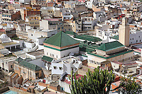 Rooftops of Moulay Idriss, with the 17th century Mausoleum of Moulay Idriss I in the foreground, Meknes-Tafilalet, Northern Morocco. The town sits atop 2 hills on Mount Zerhoun and was founded by Moulay Idriss I, who arrived in 789 AD and ruled until 791, bringing Islam to Morocco and founding the Idrisid Dynasty. It is an important pilgrimage site for muslims. Picture by Manuel Cohen