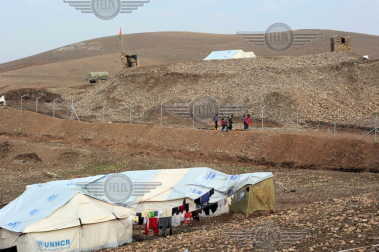 Children play near the fence surrounding the Kawergosk Syrian Refugee Camp.