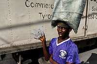 A young Haitian man sells drinking water bags on the street market in Port-au-Prince, Haiti, 7 July 2008.