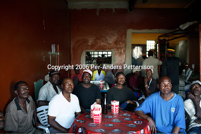 SOWETO, SOUTH AFRICA DECEMBER 9: Men drink beer and watch a soccer game on television in a bar on December 9, 2006 next to Baraghwanath taxi station in Soweto, Johannesburg, South Africa. Soweto is South Africa?s largest township and it was founded about one hundred years to make housing available for black people south west of downtown Johannesburg. The estimated population is between 2-3 million. Many key events during the Apartheid struggle unfolded here, and the most known is the student uprisings in June 1976, where thousands of students took to the streets to protest after being forced to study the Afrikaans language at school. Soweto today is a mix of old housing and newly constructed townhouses. A new hungry black middle-class is growing steadily. Many residents work in Johannesburg but the last years many shopping malls have been built, and people are starting to spend their money in Soweto.  .(Photo by Per-Anders Pettersson/Getty Images)..