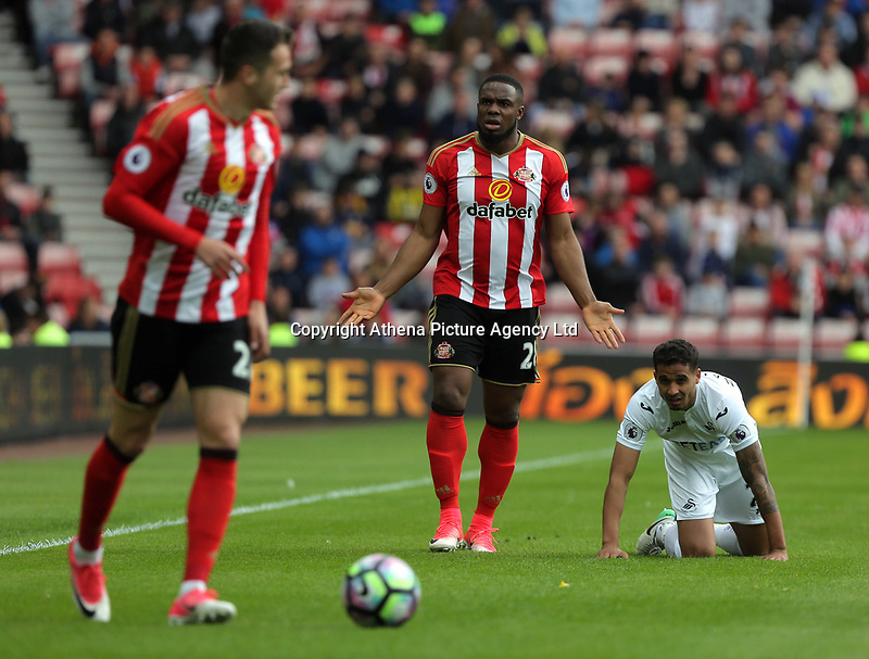 Victor Anichebe of Sunderland  (C) protests to the linesman for his foul against Kyle Naughton of Swansea City (R) during the Premier League match between Sunderland and Swansea City at the Stadium of Light, Sunderland, England, UK. Saturday 13 May 2017