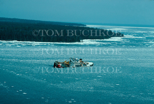 USCGC Mesquite (WLB-305) sits in the ice off Keweenaw Point in Lake Superior in March of 1990. At 2 a.m. on the morning of Monday, December 4, 1989, the 180-foot Coast Guard buoy tender Mesquite ran aground in 12 feet of the dark, icy waters of Lake Superior off Keweenaw Point in Michigan's Upper Peninsula.  With a crew of 53 aboard, the cutter was in the process of removing aids to navigation from the lake prior to winter freeze.<br /> The Mesquite suffered severe damage which caused extensive flooding of the engine room.  A list to the port side developed, and by 6:20 a.m. Lt. Cmdr. J.R. Lynch, the commanding officer, had ordered abandon ship. Severe weather following the accident left the ship in a poor condition. By mid-December the Coast Guard had determined that the cutter could not be saved.  The vessel was considered a 'constructive total loss'. <br /> It was towed the following July to Keystone Bay, a couple of miles to the west and sunk in 105 ft of water as a dive attraction.