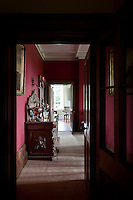 An elaborately carved sideboard is glimpsed through a doorway into the dining room