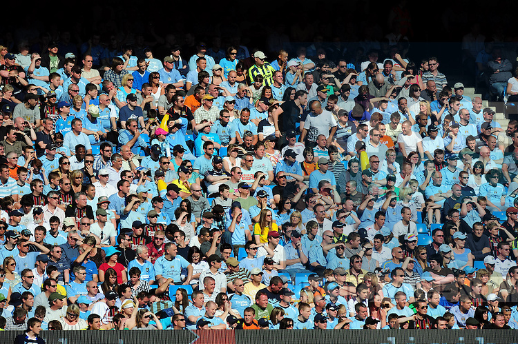Manchester City fans watching the match in the sunshine
