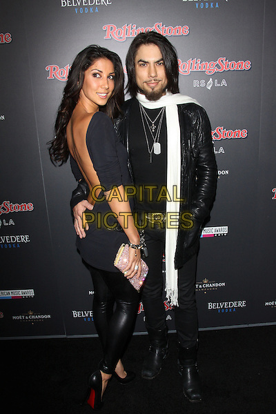 LEILANI DOWDING & DAVE NAVARRO.American Music Awards After Party Hosted By Rolling Stone Magazine held Rolling Stone Restaurant And Lounge, Hollywood, CA, USA..November 21st, 2010.AMA AMAS AMA'S full length dress black side scarf white leather jacket pink clutch bag couple backless looking over shoulder .CAP/ADM/TC.©T. Conrad/AdMedia/Capital Pictures.