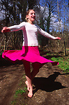 ADFRX7 Young girl dancing in woodland in springtime