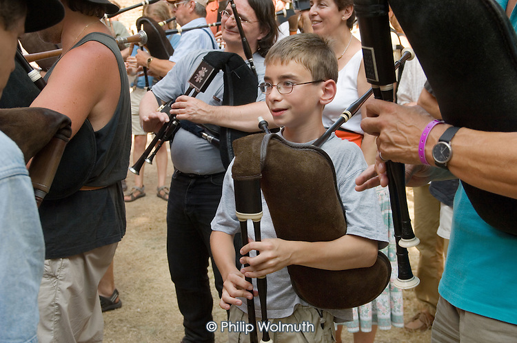 Young boy playing bagpipes at the 31st International Festival of Luthiers and Maitres Sonneurs, in Saint Chartier, France.