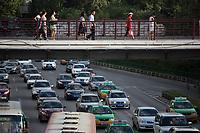 People walk in a pedestrian overpass in Xian, Shaanxi, China.