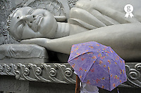 Girl with umbrella nearby lying Buddha statue, Long Son Pagoda, Nha Trang, Vietnam (Licence this image exclusively with Getty: http://www.gettyimages.com/detail/85071254 )