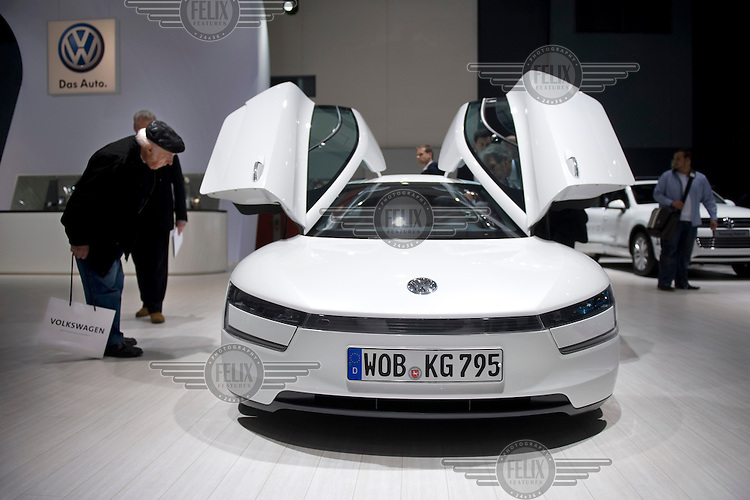 A man looks through the gull-winged doors of a VW car displayed at the annual shareholders meeting of Volkswagen AG.