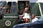 United States President Barack Obama, right chats with a U.S. Marine as his daughter Malia Obama, 16, and first lady Michelle Obama walk out of Marine One after arriving at the Martha's Vineyard Airport in West Tisbury, Massachusetts, U.S., on Saturday, August 9, 2014.  The Obama's are vacationing on the island for two weeks.<br /> Credit: Matthew Healey / Pool via CNP