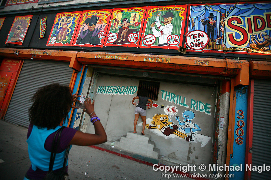 "BROOKLYN - AUGUST 04, 2008:  Akeema Bryan, 16 (L), takes a picture of her cousin Dominique Linton, 22, in front of ""The Waterboard Thrill Ride,"" an animatronic diorama of a prisoner being waterboarded in the Coney Island arcade, on August 04, 2008 in Brooklyn.  (PHOTOGRAPH BY MICHAEL NAGLE)"