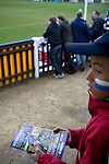 Wealdstone 0 Newport County 0, 17/03/2012. St Georges Stadium, FA Trophy Semi Final. A young fan with a programme inside St Georges Stadium, home ground of Wealdstone FC, before the club played host to Newport County in the semi-final second leg of the F.A. Trophy. The game ended in a goalless draw, watched by a capacity crowd of 2,092 which meant the visitors from Wales progressed by three goals to one to the competition's final at Wembley, where they would meet York City. The F.A. Trophy was the premier cup competition for non-League clubs in England and Wales affiliated to the Football Association. Photo by Colin McPherson.