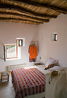 In this bedroom the quirky windows are original to the house and a vivid Moroccan throw adds a splash of colour to the white-painted walls