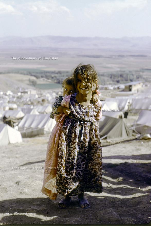 Iran 1974.Camp de réfugiés kurdes à Nelliwan, une fillette portant son petit frère sur le dos.Iran 1974.Kurdish refugees' camp, a young girl and her brother on her back
