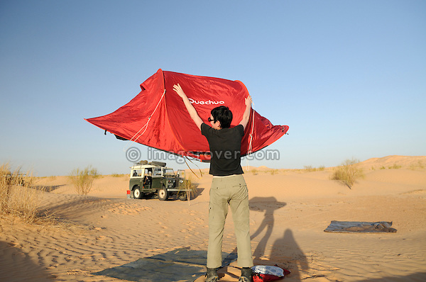 Africa, Tunisia, nr. Tembaine. Desert tourist Kerstin putting up a modern Quechua tent. --- No releases available, but releases may not be needed for certain uses. --- Info: Image belongs to a series of photographs taken on a journey to southern Tunisia in North Africa in October 2010. The trip was undertaken by 10 people driving 5 historic Series Land Rover vehicles from the 1960's and 1970's. Most of the journey's time was spent in the Sahara desert, especially in the area around Douz, Tembaine, Ksar Ghilane on the eastern edge of the Grand Erg Oriental.