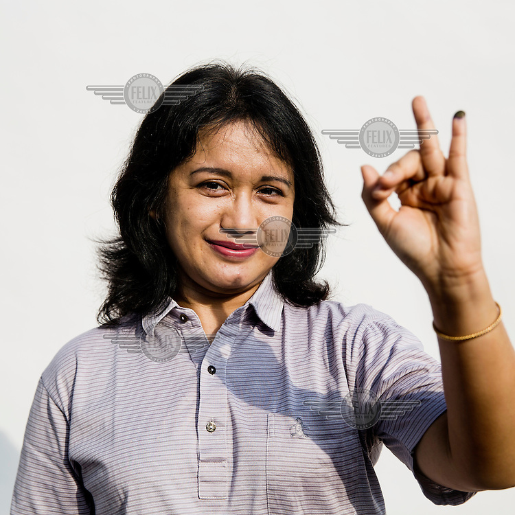 A woman flashes a two fingered sign, symbolising Indonesian presidential candidate Jokowi's candidacy number after she casts her vote at a polling station in Jakarta.