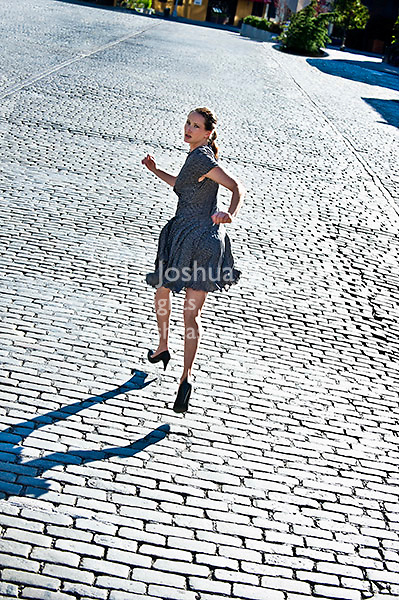 Woman running down cobblestone street, rear view