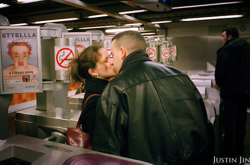 Couple kisses at the ticket gates of Paris' Republique metro station..Picture taken 2005 by Justin Jin