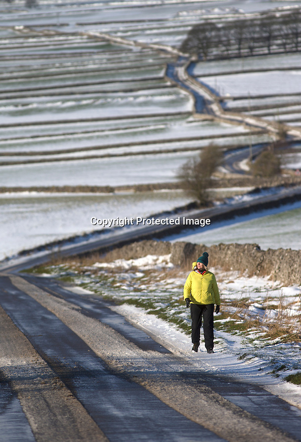 13/01/17<br />  <br /> A walker passes is framed by symmetrical dry stone walls and snowy fields near Hartington in the Derbyshire Peak District.<br /> <br /> All Rights Reserved F Stop Press Ltd. (0)1773 550665   www.fstoppress.com