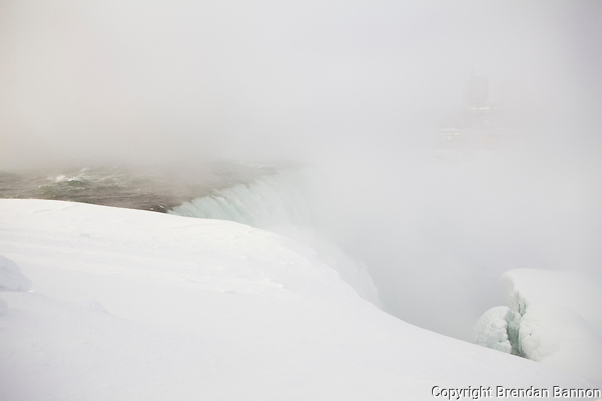 The brink of the falls as water pours toward a towering ice mound. The ice mounds in the river below the falls can last until May. Niagara Falls from the American side. Brendan Bannon.