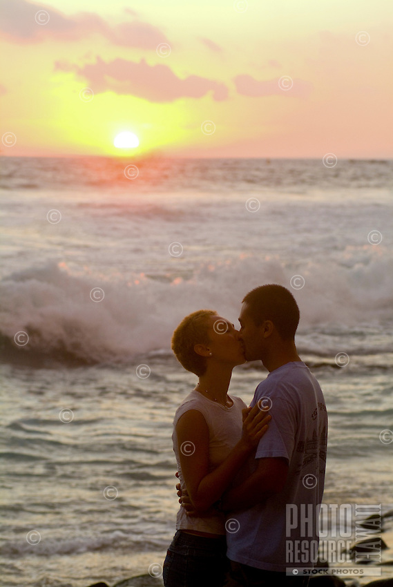 A couple kisses on Hano beach in Kona with a glowing sunset and waves breaking behind them.