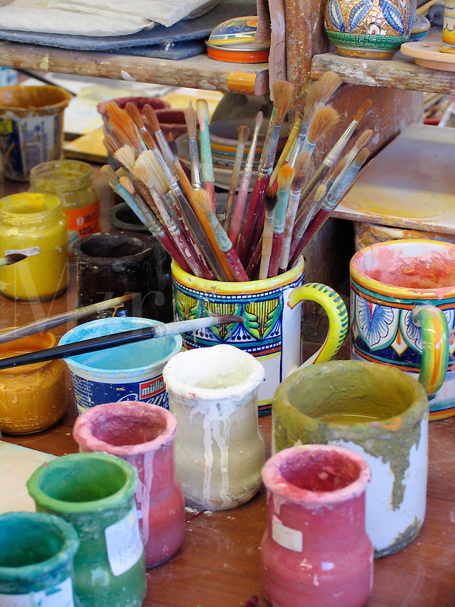 paint brushes and paints on workbench in ceramics factory in Deruta, Ital