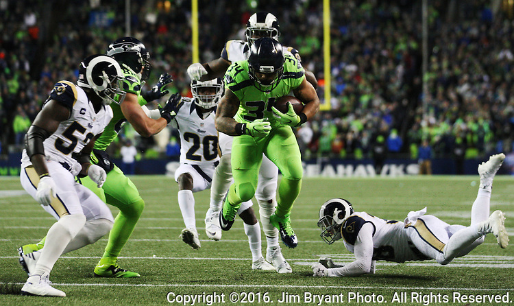 Seattle Seahawks running back Thomas Rawls (34) breaks tackles by Los Angeles Rams defensive back Cody Davis (38) on his way to a 12-yard gain at CenturyLink Field in Seattle, Washington on December 15, 2016.  The Seahawks beat the Rams 24-3.   ©2016. Jim Bryant Photo. All Rights Reserved