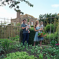 Francesca and Dominic Rowan stand with their sons in the vegetable garden which is situated to the rear of Lamb House