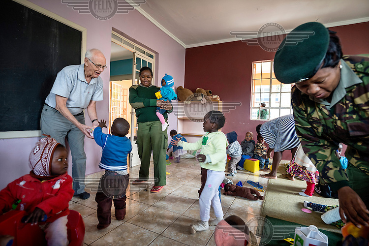 A prison officer and Father Peter Meienberg playing with children in the daycare centre at Langata Women's Prison. The centre was built by the Faraja Foundation, under the leadership of its founder Father Peter. Children living with their mothers in prison and on remand spend the day in the centre while their mothers can work. Some of the women prisoners help by preparing food, playing games, putting the young ones to bed and cleaning the centre.