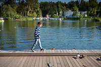 Boy walking on boardwalk near pond in Gorky park, Moscow, Russia