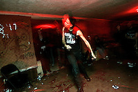 Javier Morales, guitar player of suburban Chicago band The Heretics, dances during a concert in the basement of the White House in Woodstock, Illinois.   The White House was a small suburban residential home rented by a group of 20-somethings in Woodstock, Illinois, a distant northwestern suburb of Chicago.  For about a year, the renters of the house staged punk-rock concerts in the house's small basement, without the approval of the neighborhood, local government, or police.  .