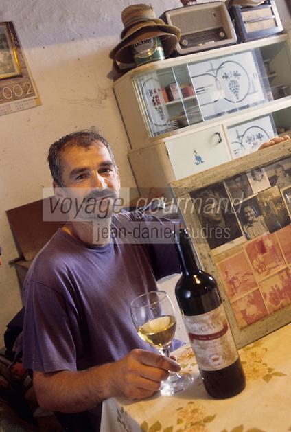 Europe/Croatie/Dalmatie/ Ile de Vis/ Komiza:  Ante Ivcevic viticulteur  déguste son vin devant les photos de famille