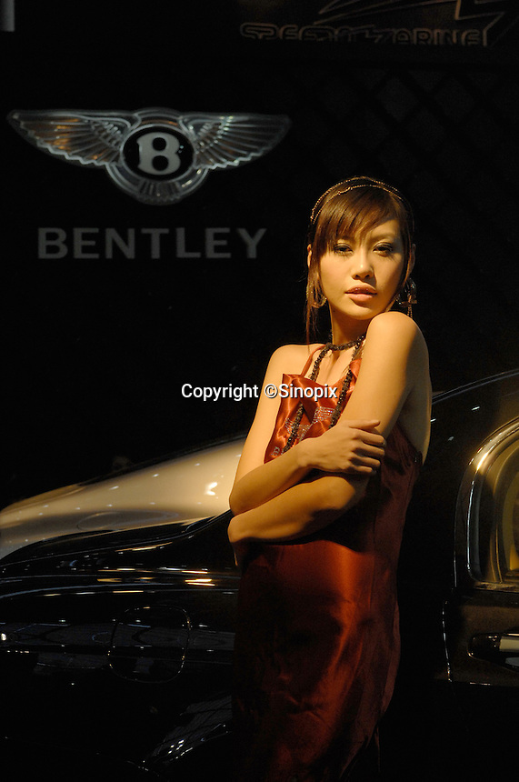 """A model drapes herself across a Bentley at the """"Top Show"""" luxury goods fair in Shenzhen, China."""
