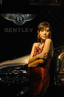 "A model drapes herself across a Bentley at the ""Top Show"" luxury goods fair in Shenzhen, China."